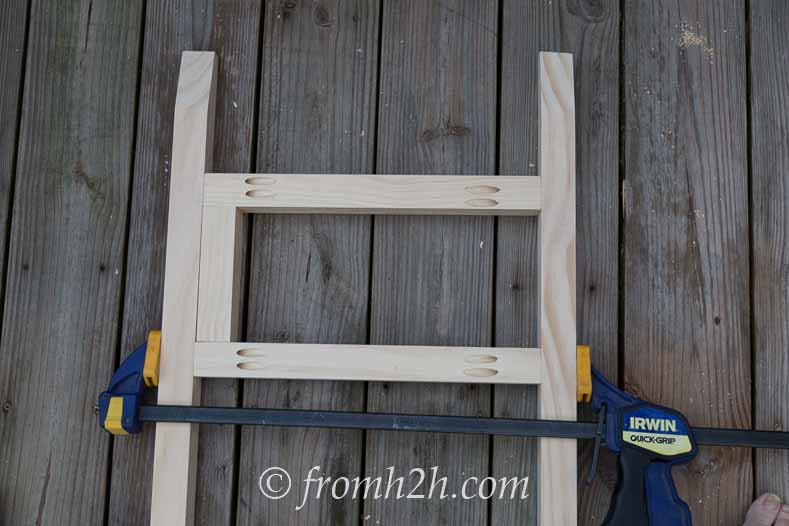 Use a clamp to keep the boards in place | DIY Fabric Storage Ladder