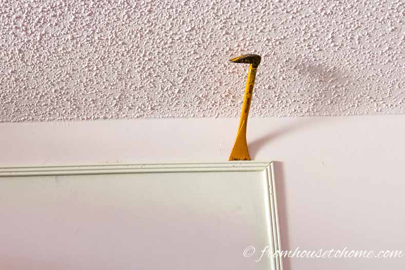 Use a moulding bar to pry the mouldings away from the wall