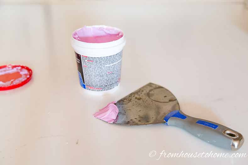 Scoop up spackling with putty knife