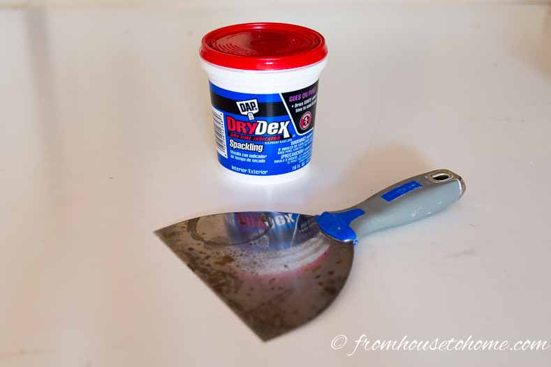 Use spackle and a putty knife to fill any holes | How To Hang Wallpaper The Easy Way