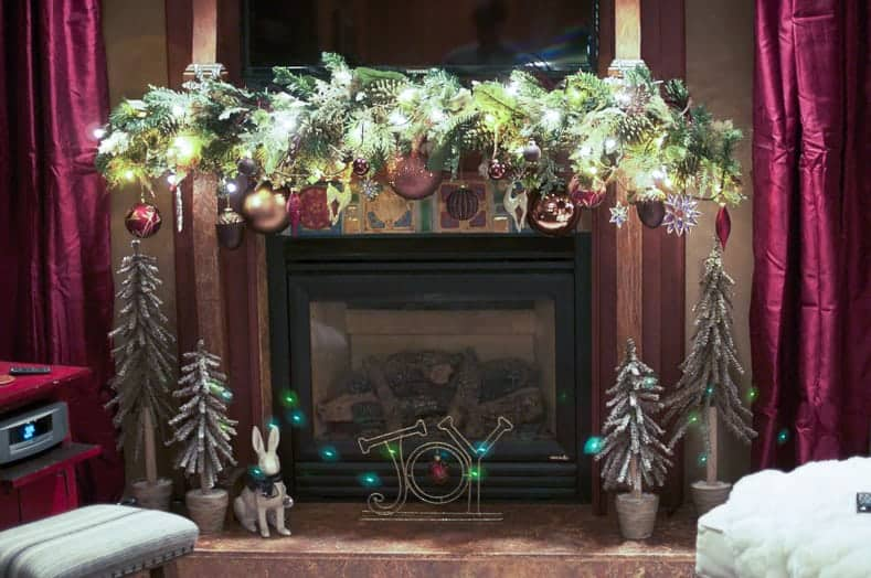 A garland with large ornaments hanging down draws your attention down to the Christmas decorations in front of the fireplace (via alveo.co) | How To Decorate a Christmas Mantel With a TV Above It