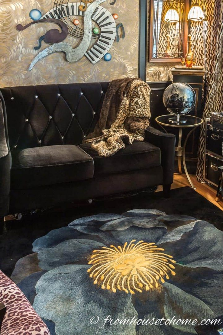 Black and blue area rug in front of a black velvet sofa