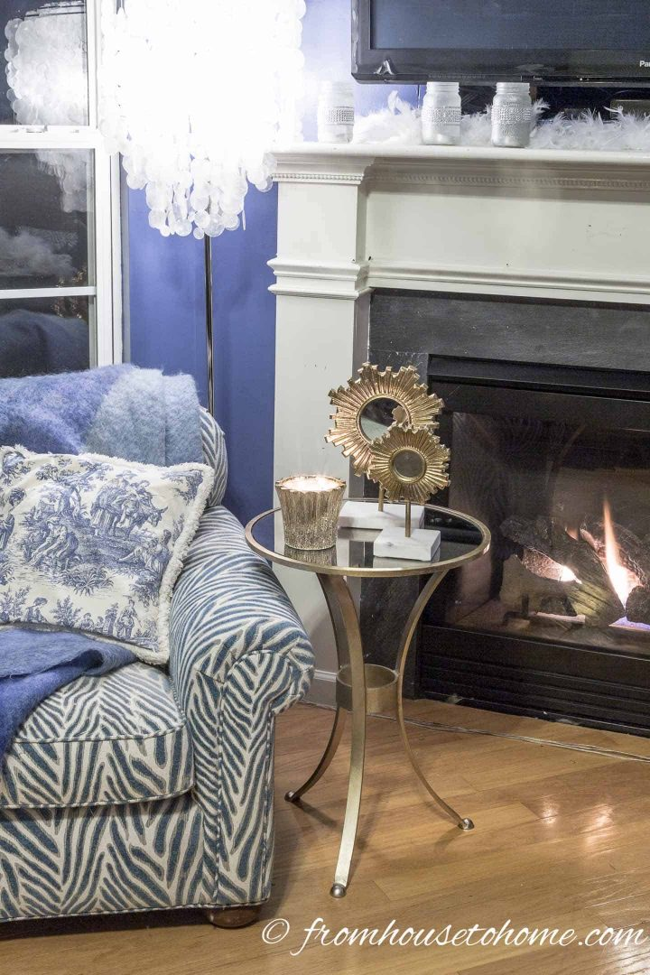 Blue and white arm chair beside the fireplace