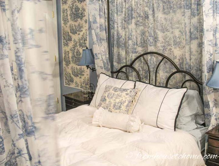 Canopy bed with blue and white toile curtains