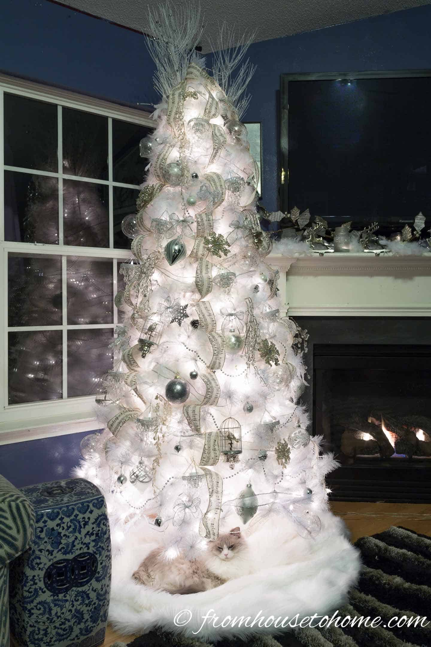 White cat under an all white Christmas tree