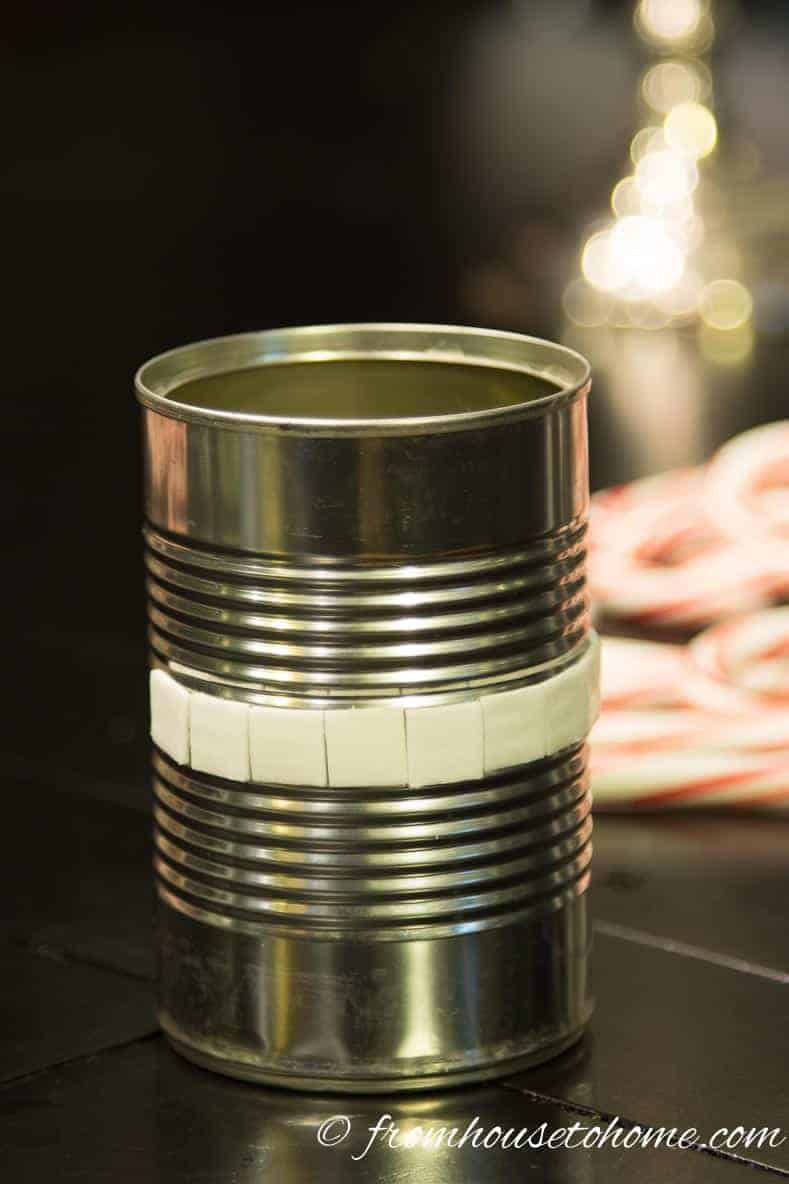 Stick double-sided tape around the middle of the tin can | Learn how to add some Christmas spirit to your table with a DIY candy cane centerpiece! | DIY Quick and Easy Candy Cane Centerpiece