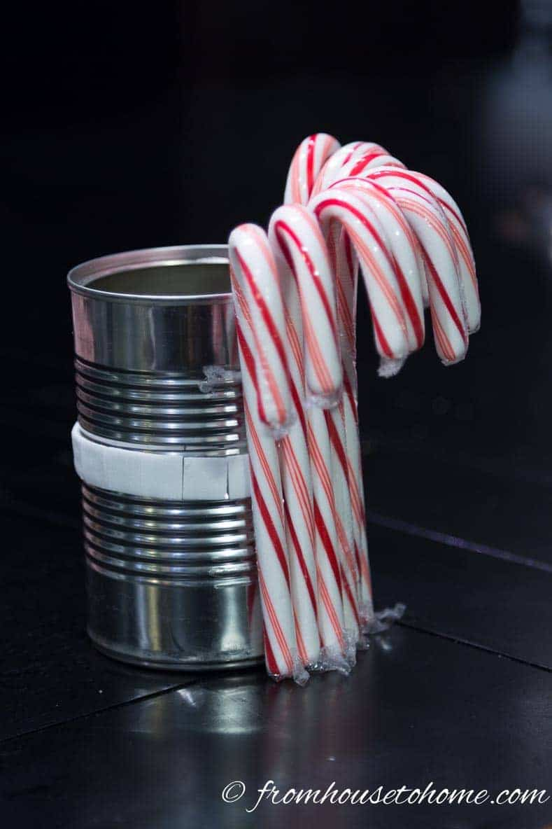 Stick the candy canes onto the double sided tape | Learn how to add some Christmas spirit to your table with a DIY candy cane centerpiece! | DIY Quick and Easy Candy Cane Centerpiece