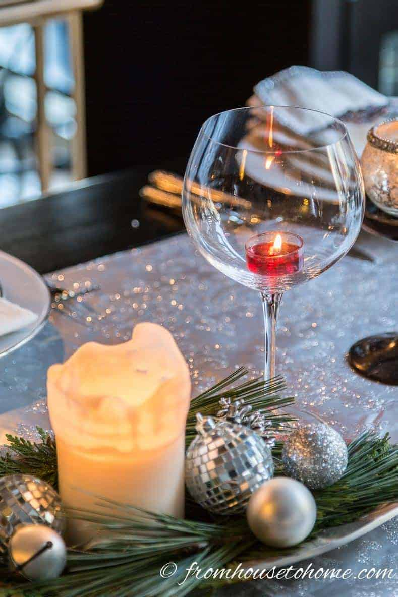 A wine glass used as a candle holder with a tealight candle