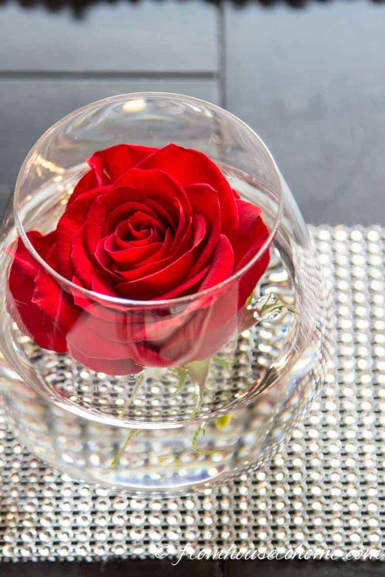 A stemless wine glass used as a vase with a red rose