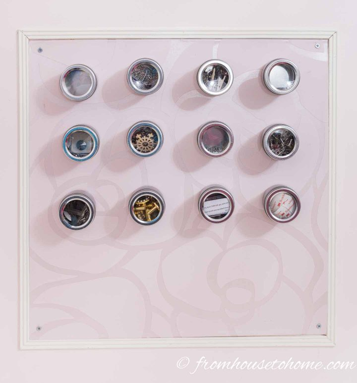 Pins, buttons, hooks and other craft room and sewing accessories stored in containers on a magnetic bulletin board hung on the craft room wall