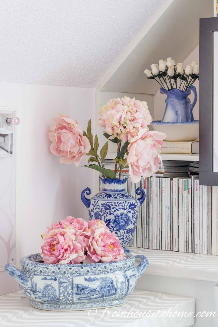 Faux flowers stored in vases on a craft room shelf
