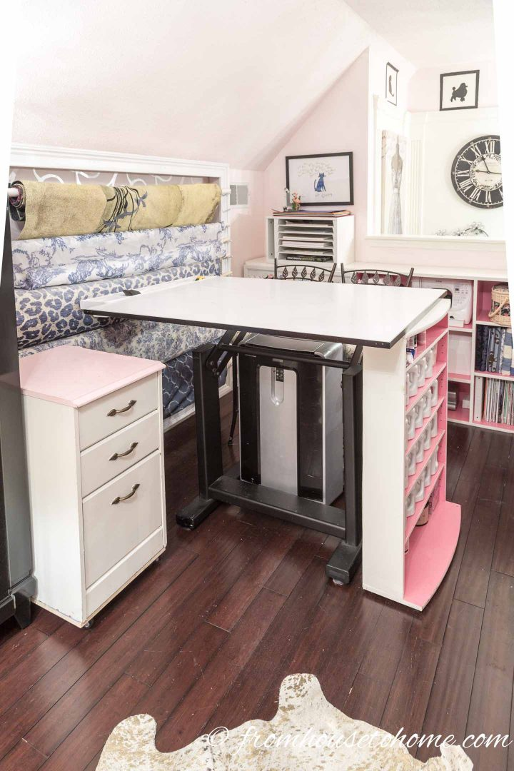 Mobile filing cabinet, fabric bolts on a wall rack, craft room table and paint storage in an organized craft room