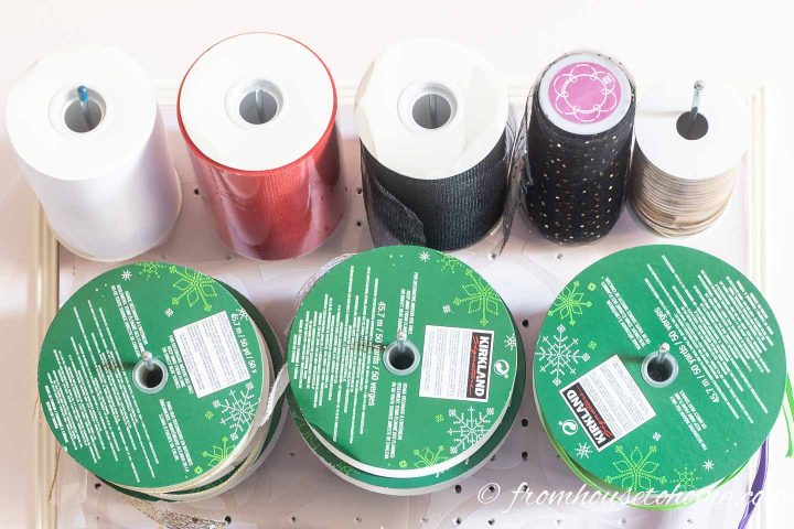 Tulle and large ribbon rolls stored on straight hooks on a craft room pegboard