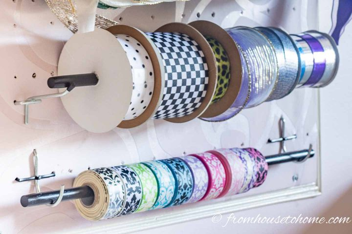 Ribbon hung on dowels on a craft room pegboard