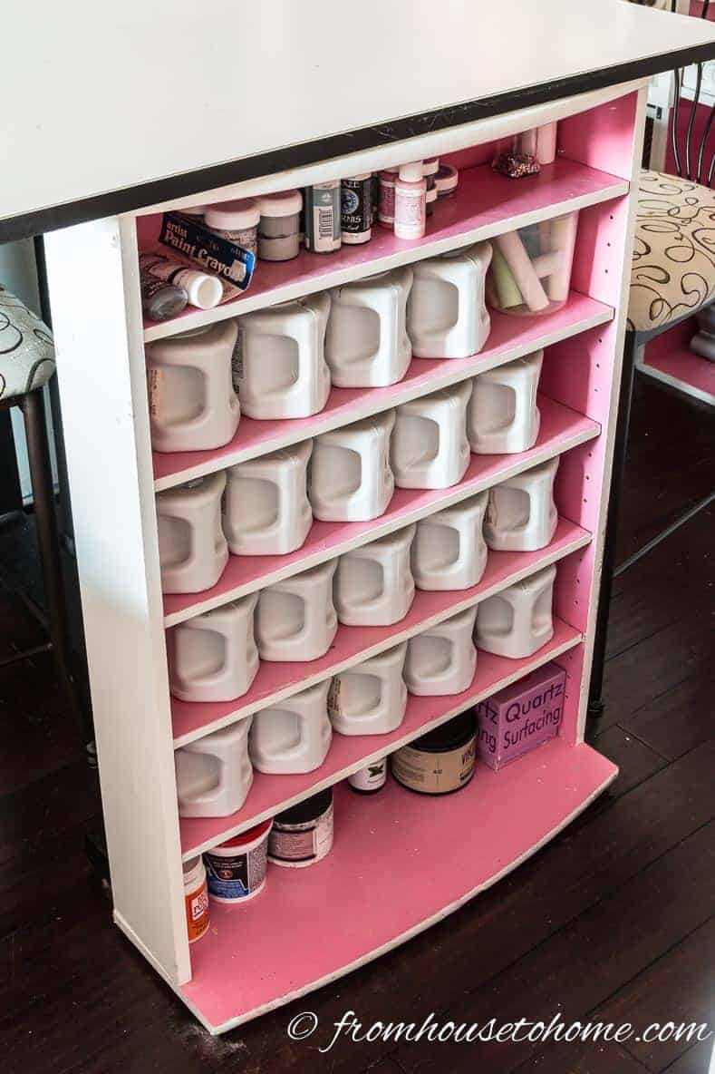 Craft room paint and other supplies stored in a re-purposed CD rack