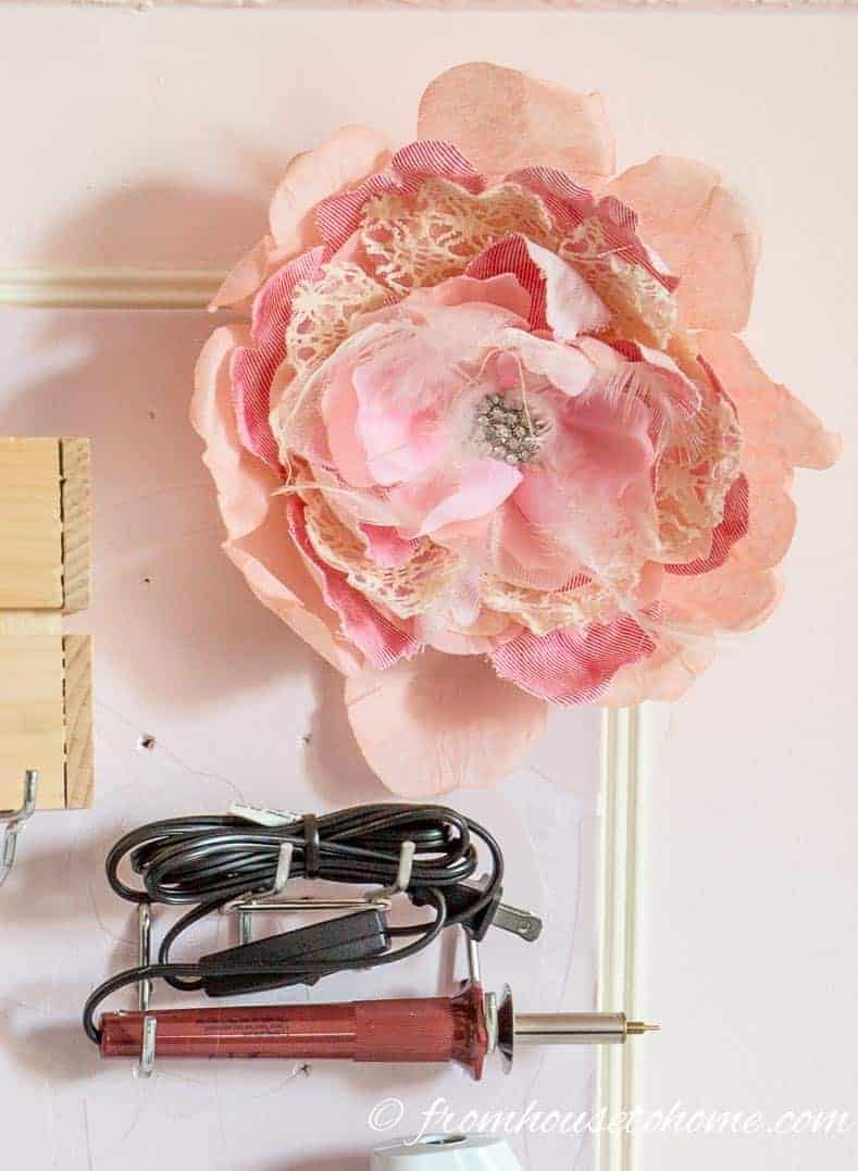 Store faux flowers by pushing the stem through the pegboard holes | 10 Simple Craft Room Organization and Storage Ideas | If you're looking for easy ways to organize your crafting supplies on a budget, these DIY storage and organization tips and ideas are perfect.