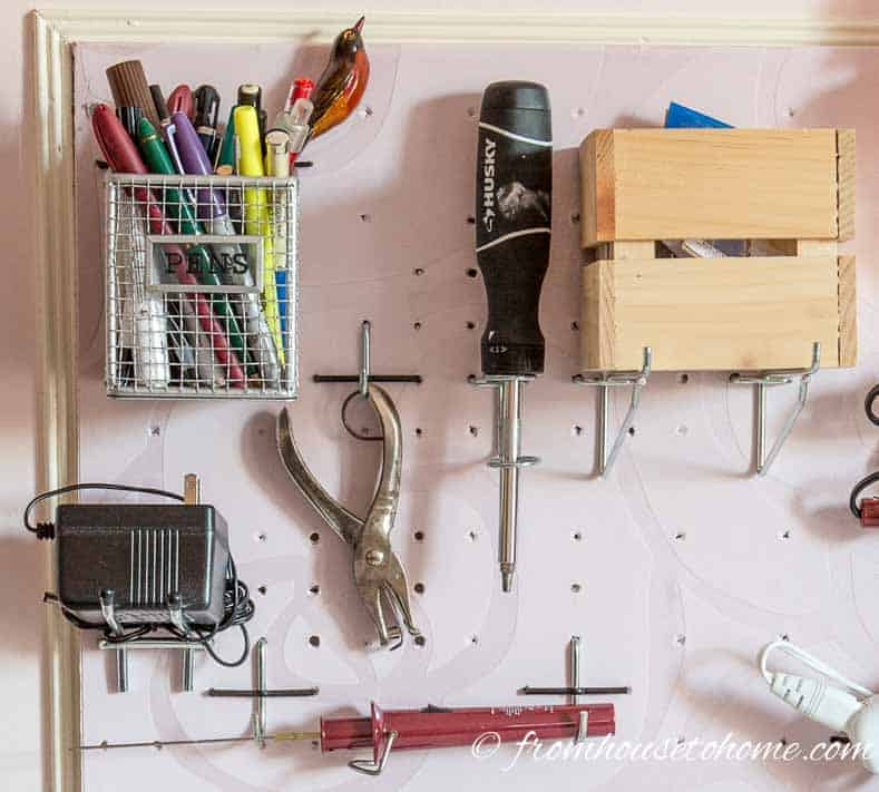 Boxes hung on pegboard shelf hooks for craft room organization