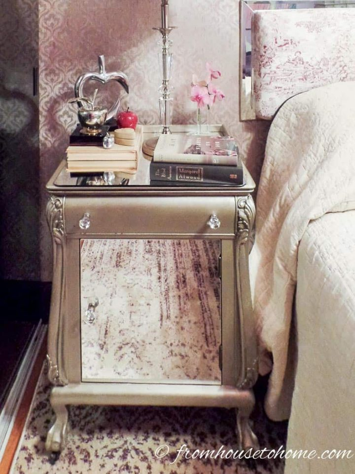 Old nightstand that has been painted silver with mirror door front and top