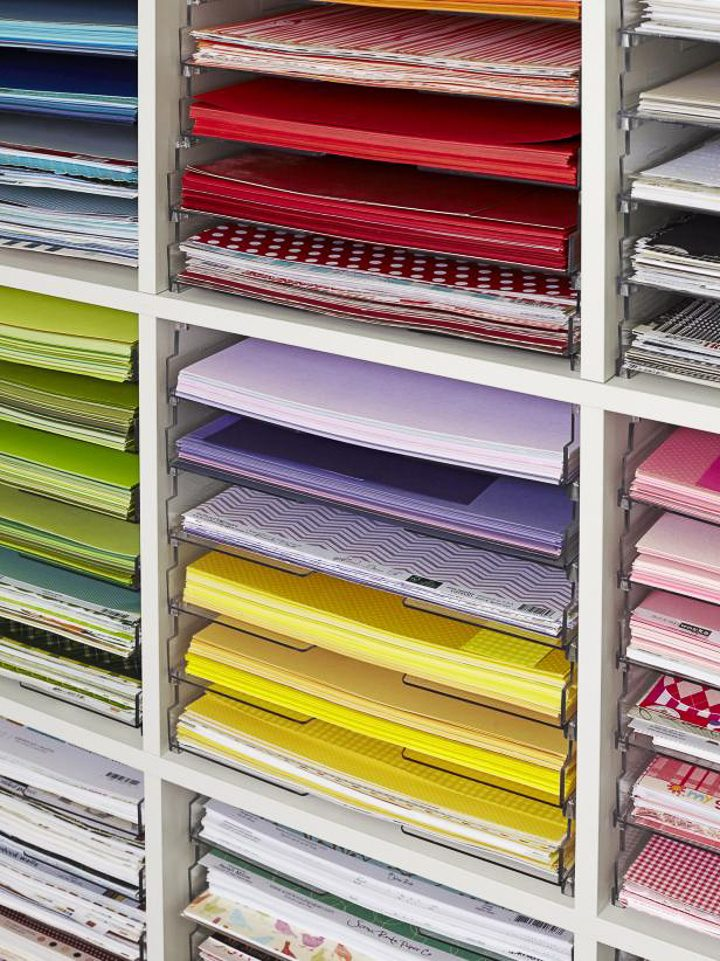 Colorful sheets of paper organized in clear paper trays for craft room storage (via hgtv.com)