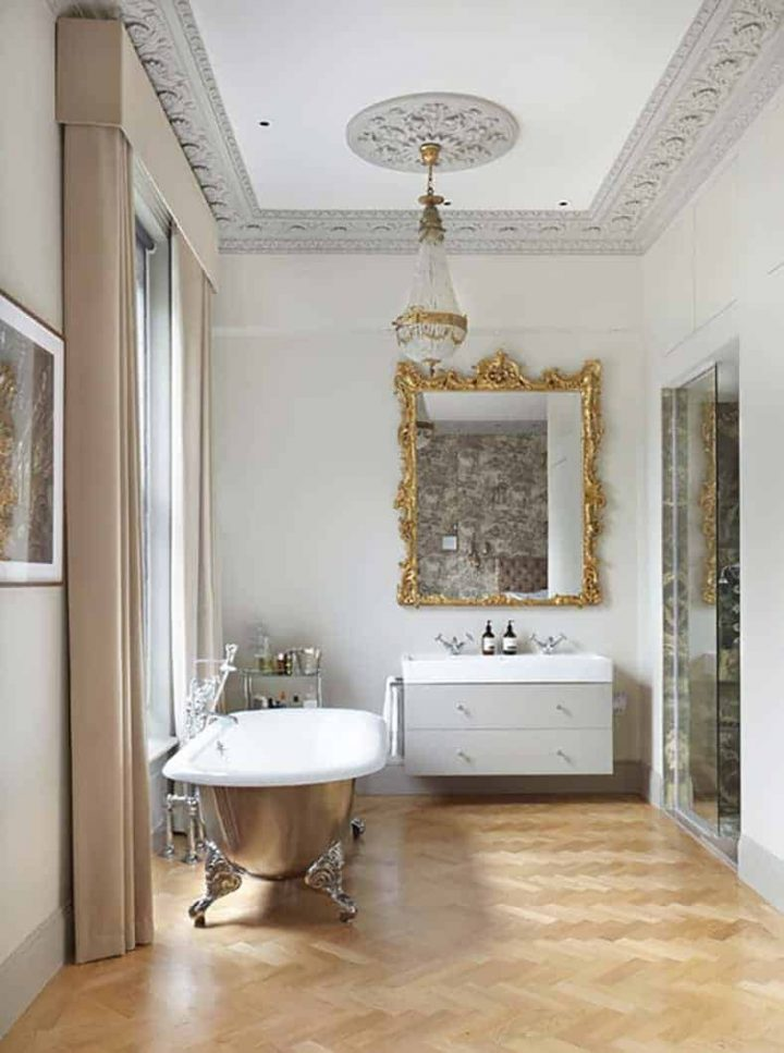Bathroom with a silver clawfoot tub and a gold mirror