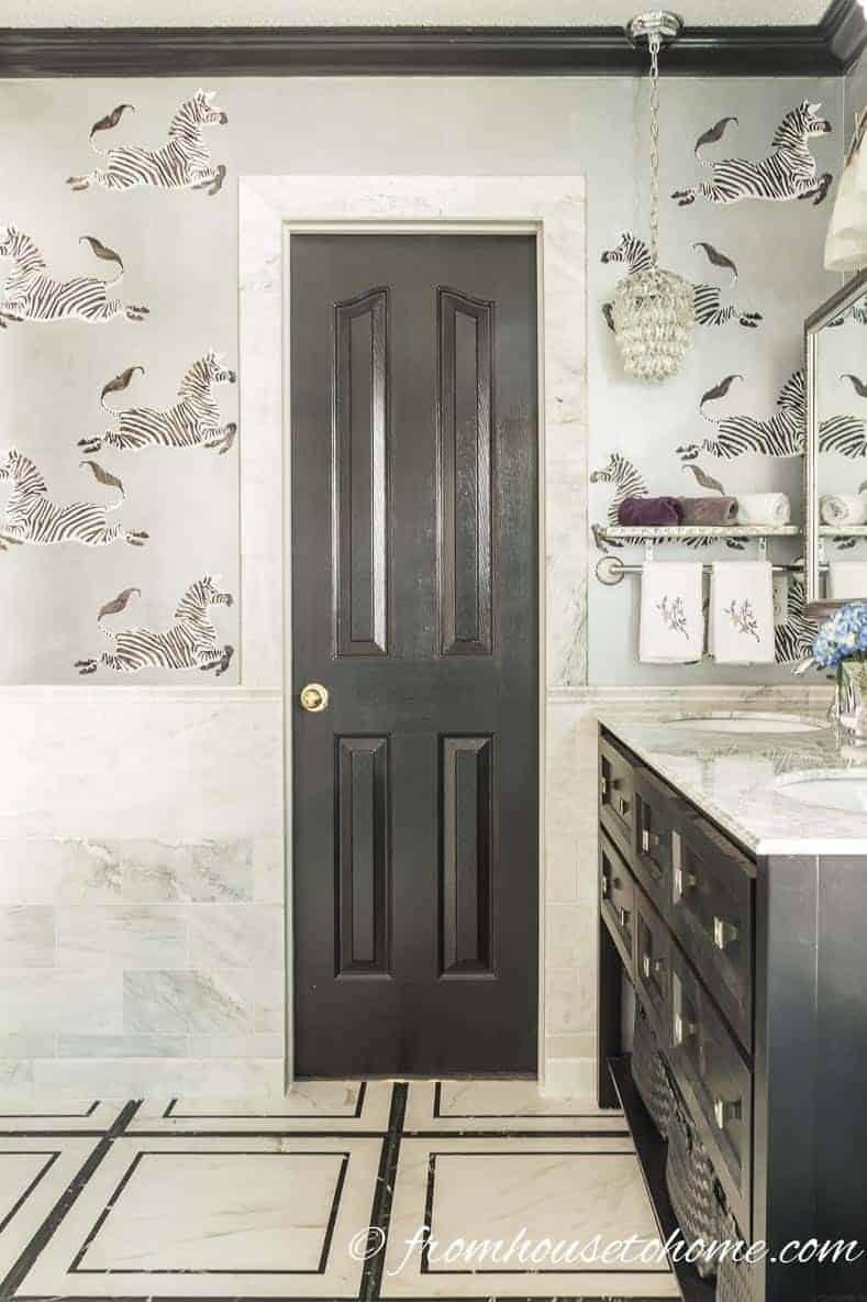 Walls painted silver with marble tile and black accents in a glam bathroom