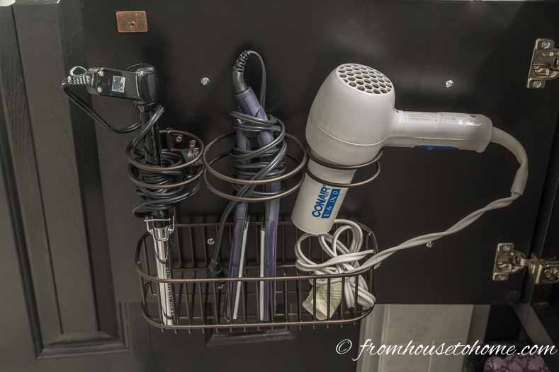 Hair dryer and curling iron organizer hung on a bathroom cabinet door