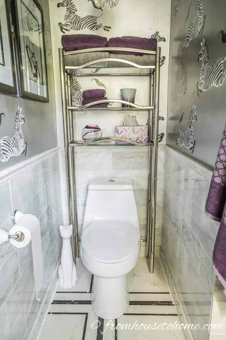 Over the toilet shelving unit that stores towels and candles
