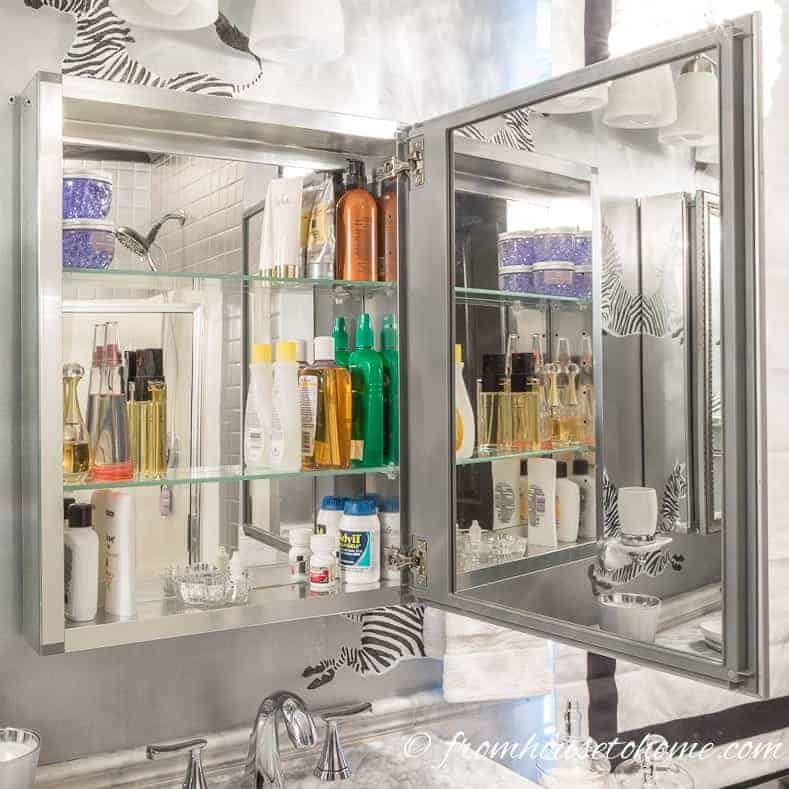 Mirrored medicine cabinet with glass shelves in a silver and white bathroom