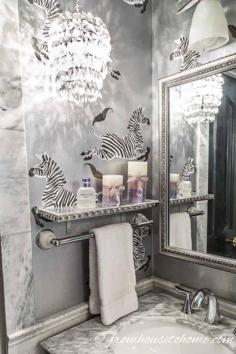 DIY Bathroom shelving that displays perfume bottles and candles