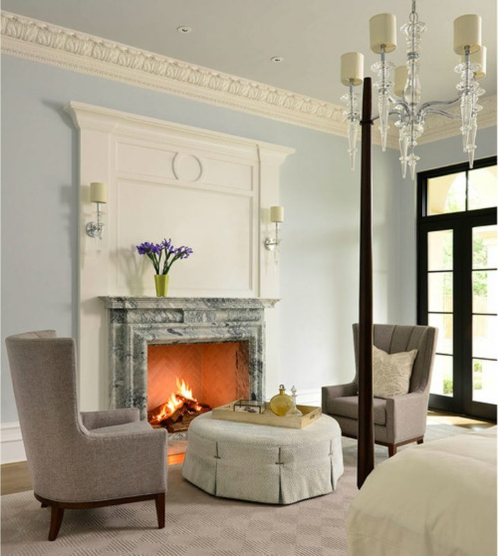 Bedroom with fireplace that has a large surround