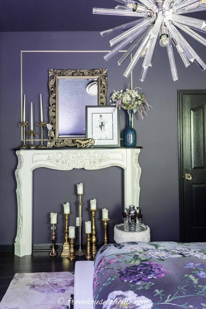 Purple bedroom with a white fireplace mantel