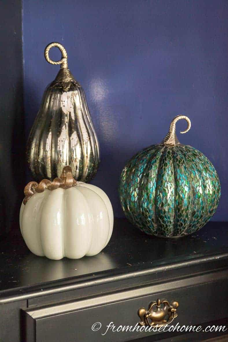 Three ceramic pumpkins displayed on a table top