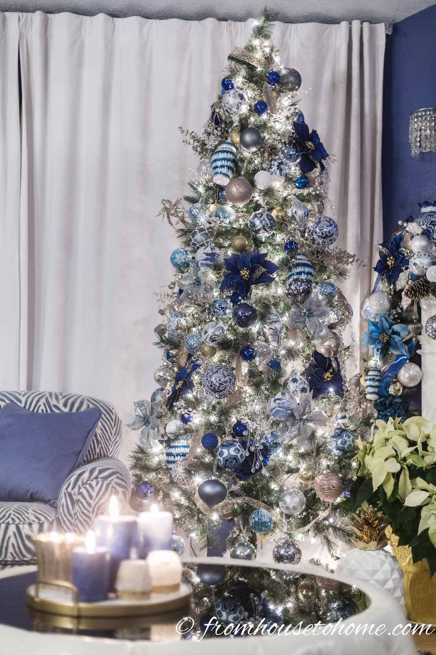 Christmas tree decorated with blue and white Christmas ornaments including blue poinsettias, and mini blue and white ginger jars
