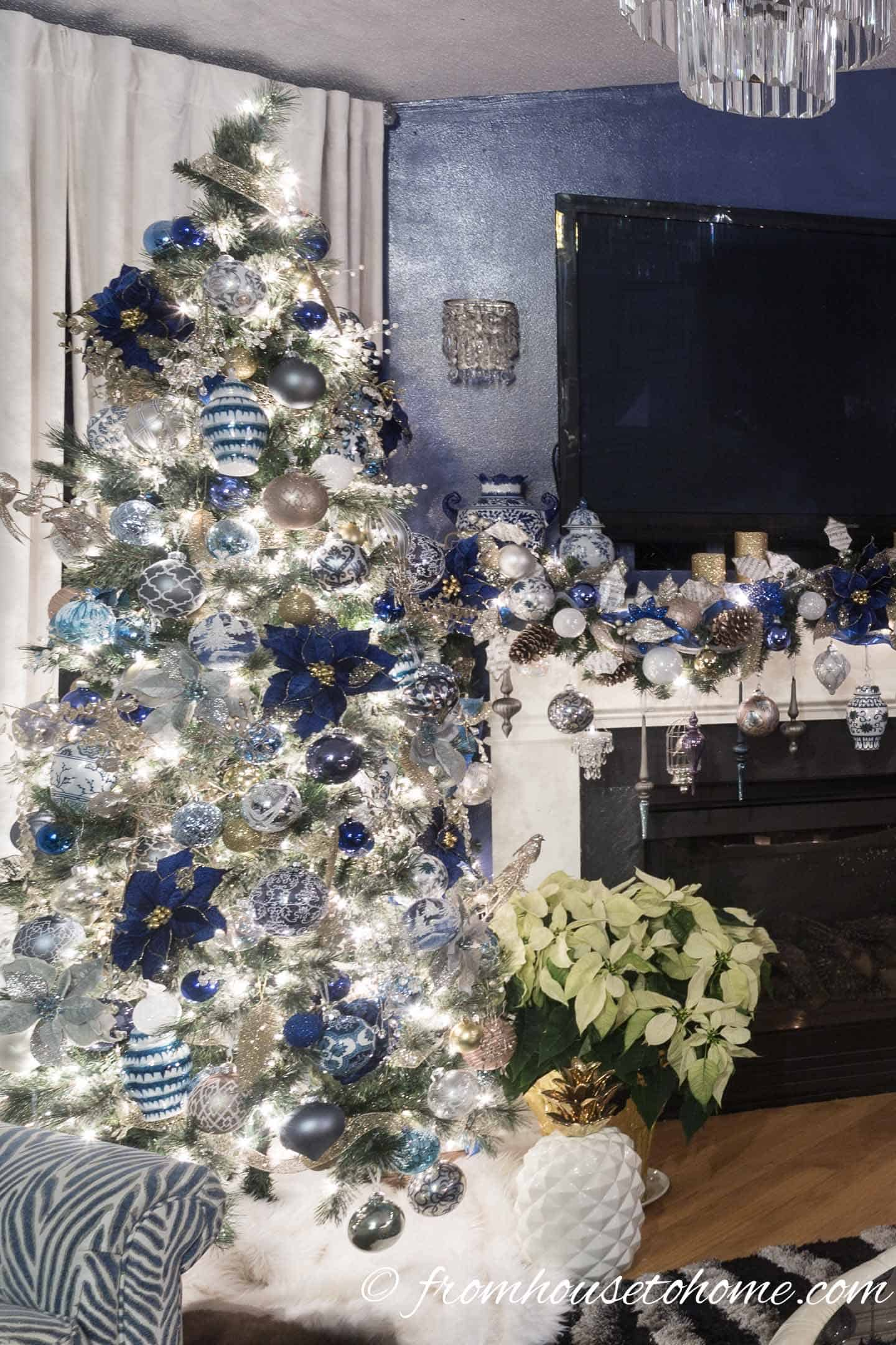 Blue and white Christmas tree beside a fireplace with a blue and white garland