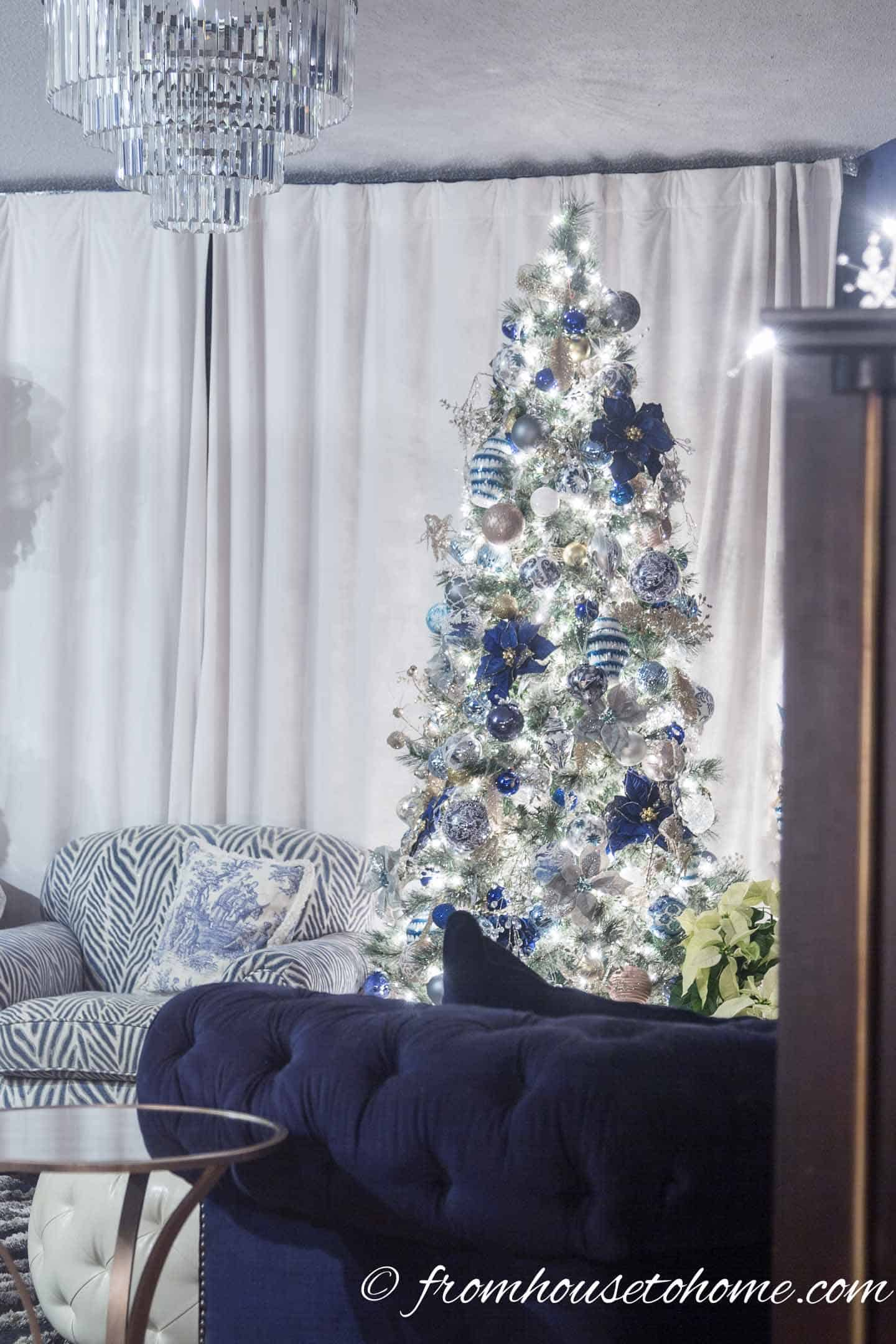 Blue and white Christmas tree behind a blue sofa