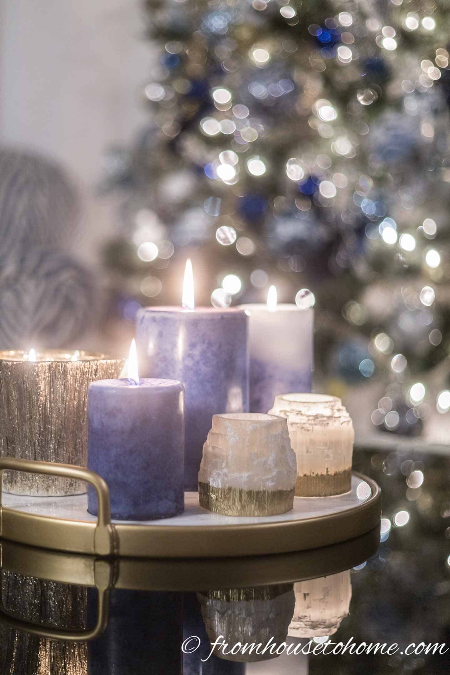 Blue, white and gold candles with a christmas tree in the background
