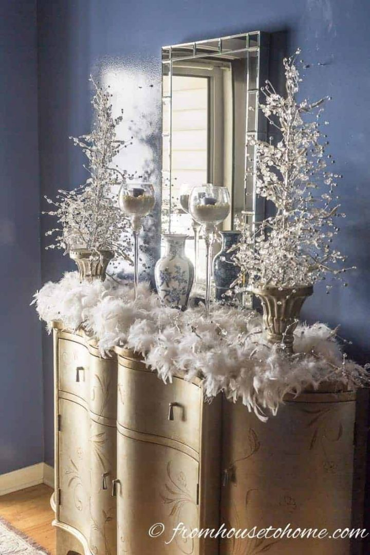 Feathers and lights Christmas decor on a console table