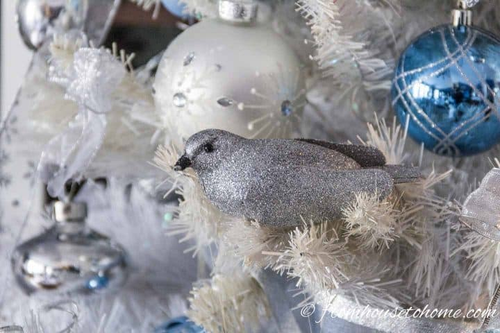 silver, white and blue ornaments on a white Christmas tree