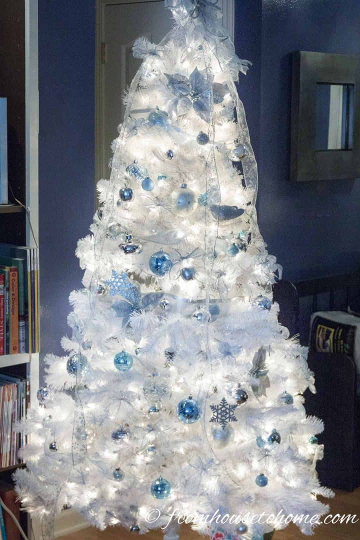 This is another version of a white, blue and silver tree with light blue ornaments, white vertical ribbons and silver bows on an all-white Christmas tree.