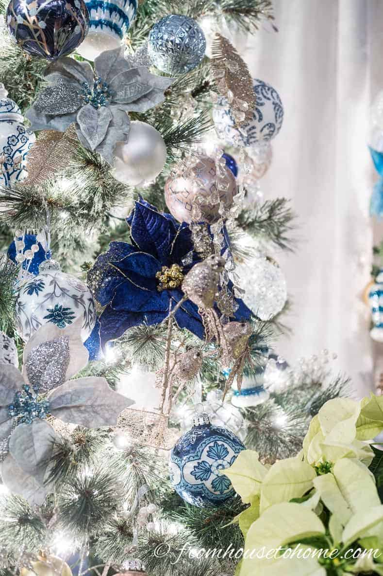 Blue poinsettia ornaments on the Christmas tree | 40 Stunning Ways to Decorate a Christmas Tree
