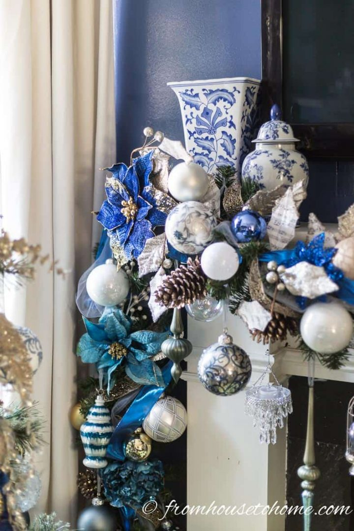 Blue white and gold Christmas garland on a fireplace mantel with blue and white ginger jars in the corners