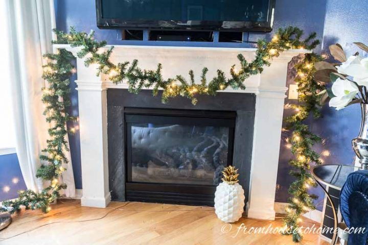 Evergreen garland with string lights on the mantel