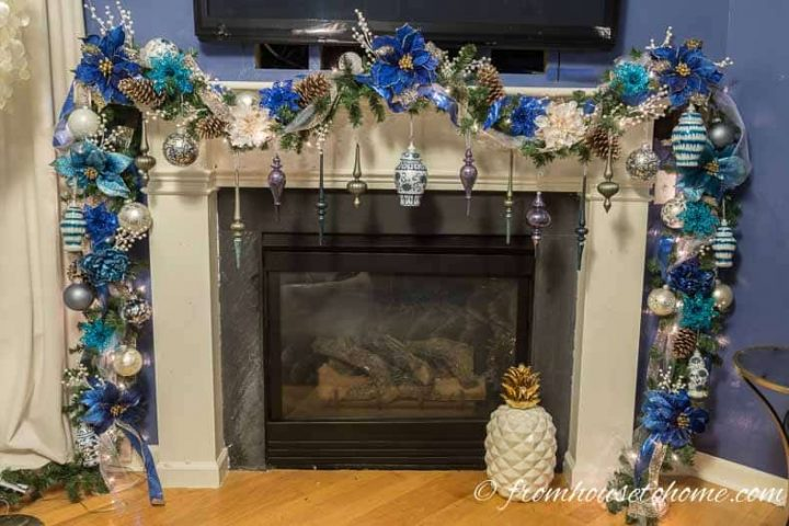 Blue, white and gold garland with large Christmas ornaments hung from it