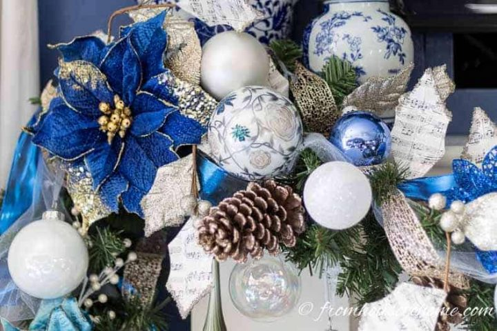Blue, white and gold garland with a lot of Christmas ornaments on the mantel