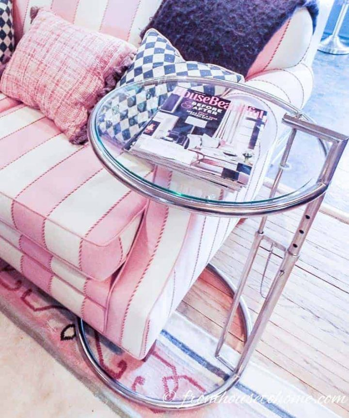 Eileen Gray glass table over the arm of a pink and white sofa