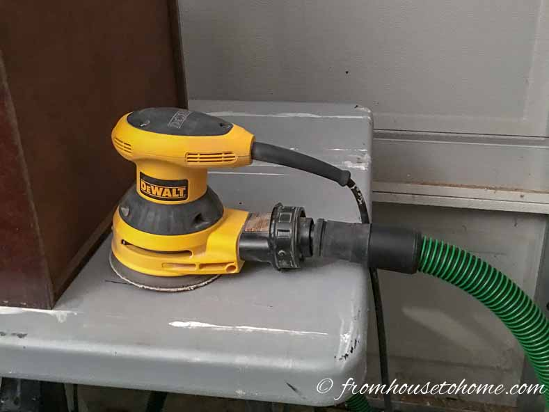 The dust collector hose attaches to the sander where the dust bag normally goes
