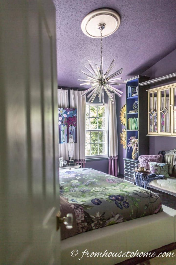 Bedroom with a purple ceiling and a gold ceiling medallion over a sputnik chandelier