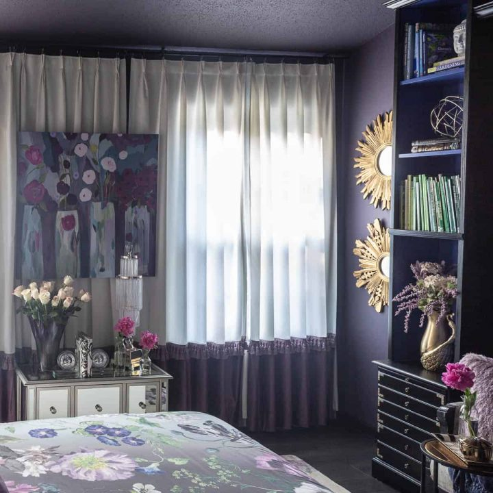 Floor to ceiling white and purple curtains in a bedroom