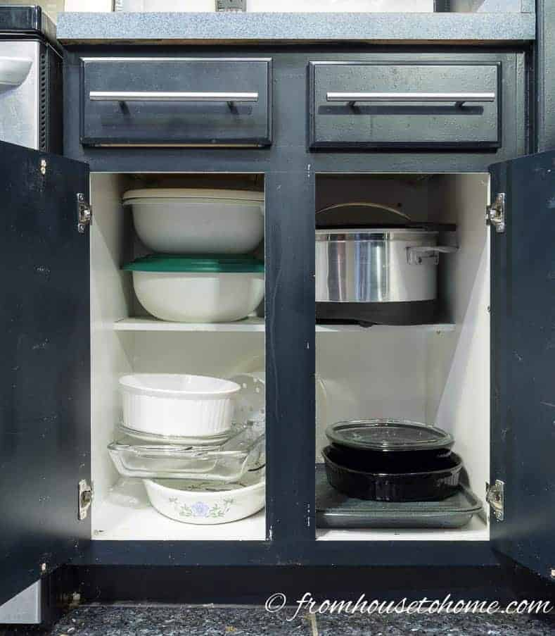 Dishes stacked in a base kitchen cabinet with doors