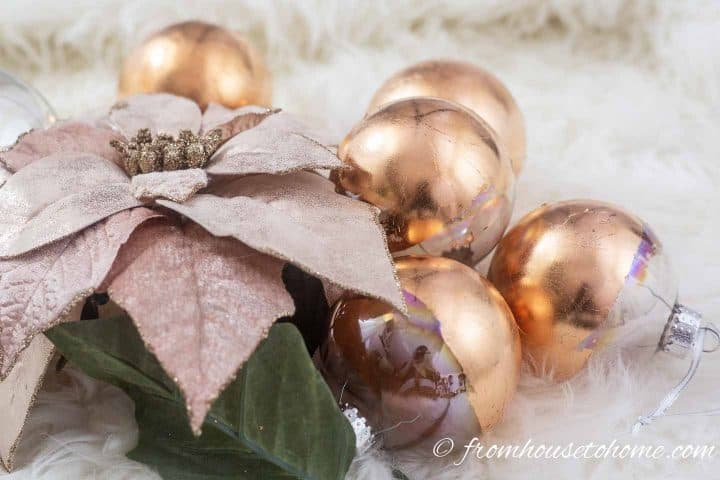 DIY copper Christmas ornaments with a pink poinsettia flower